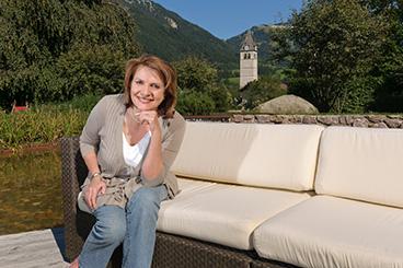 Inhaberin Kornelia Grundmann sitzt in einem Garten in Kitzbühel auf einer Couch