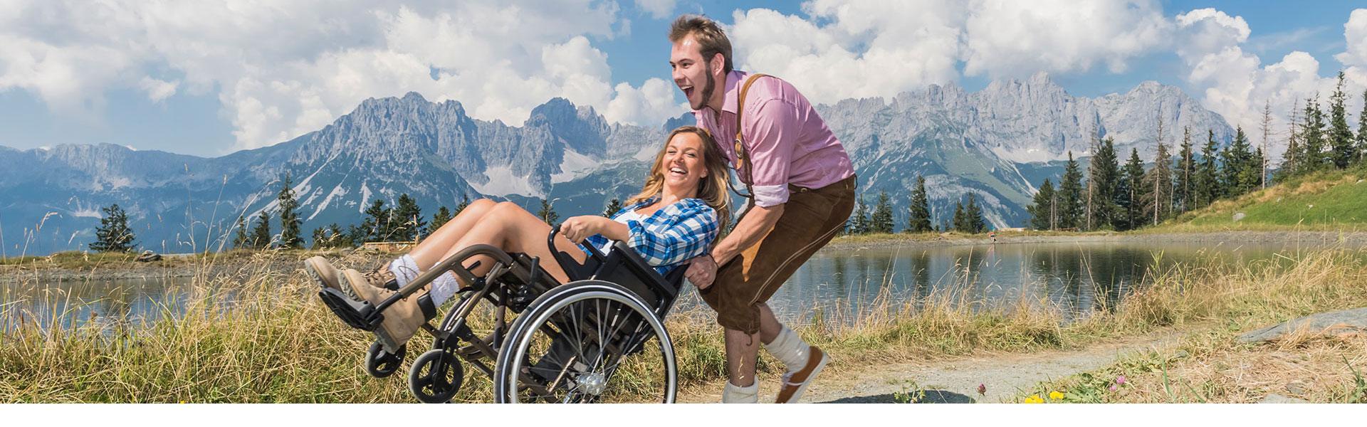 Junges Paar im Rollstuhl an einem Bergsee mit dem Wilden Kaiser im Hintergrund
