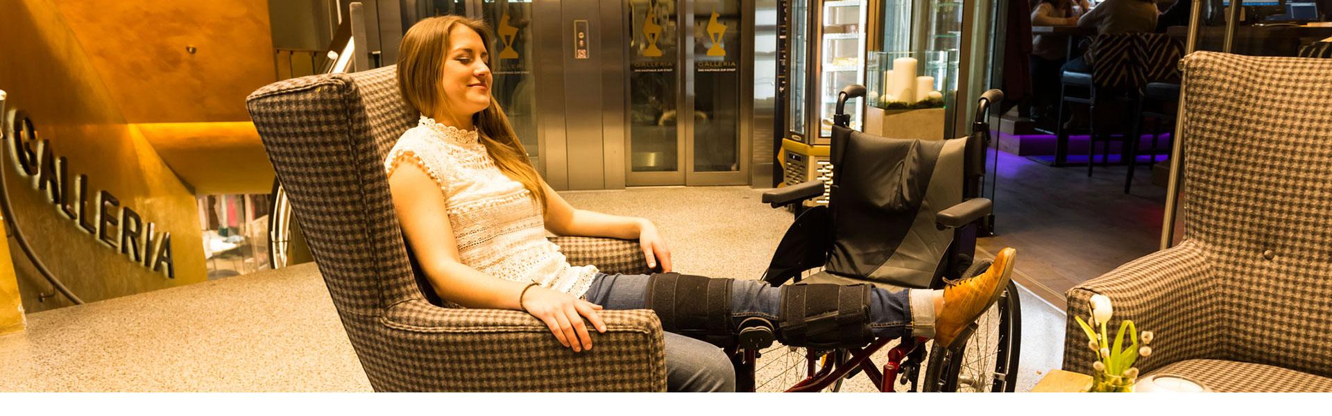 Junge Frau im Rollstuhl, Bein hochgelagert, in der Kitz Galleria (c) multivisual Art / Martin Raffeiner