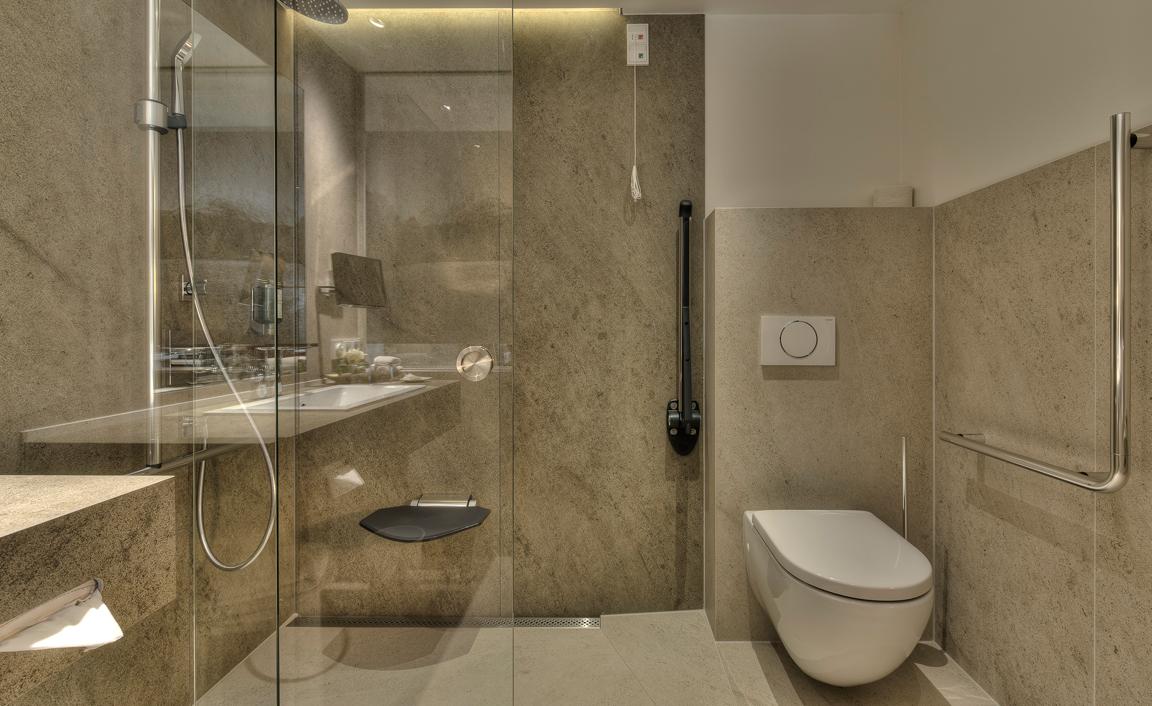Großzügiges Badezimmer mit bodengleicher Dusch und Haltegriffen am WC © Bichlhof