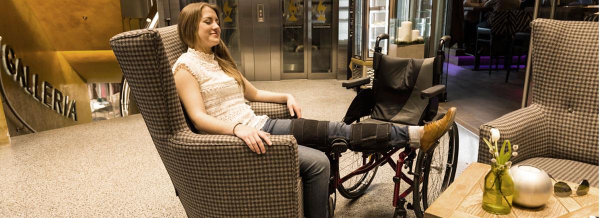Lächelnde junge Frau mit langen Haaren sitzt in einem Ohrensessel, neben ihr ein Rollstuhl. Sie hat ihr linkes Bein hochgelagert, da es geschient ist (c) multivisualart